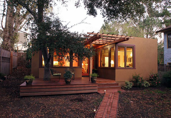 Exterior of 540 square foot home in the rear garden of a Berkeley residence, showing deck with oak tree and trellis.