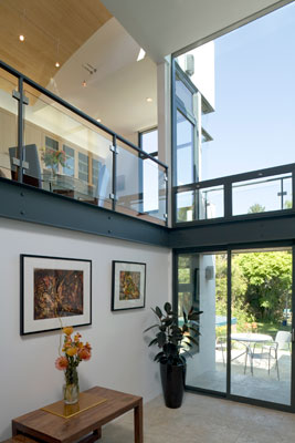 Double height atrium with floor to ceiling glass looking onto rear garden.