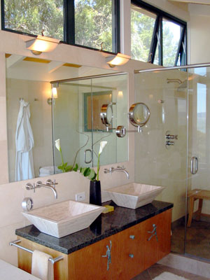 Double vessel sinks and glass enclosed shower.  Clerestory windows bring in natural light