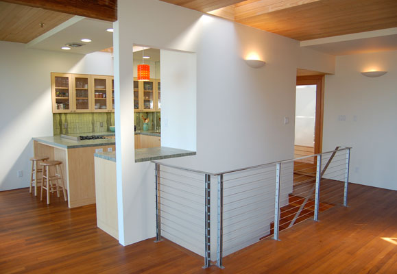View from living room into kitchen, showing the open floor plan, new steel cable stair railing and entry.