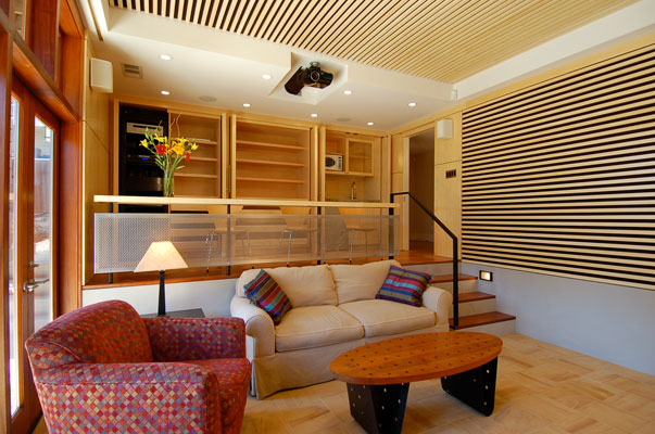 Home theater, looking at upper level and storage when open.  This storage wall houses a media center, game cabinet and wet bar.  Custom Bamboo paneling and acoustic baffles complement India Teak tiles and cherry flooring.